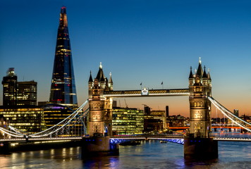 Elevated view shows the Shard and Tower Bridge standing tall above the River Thames at dusk.