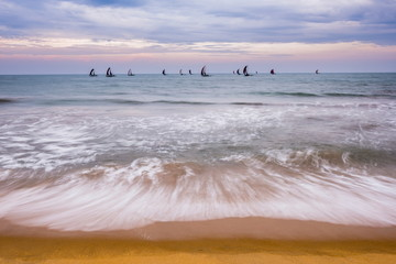 Negombo, traditional outrigger fishing boats (oruva) returning at sunrise to Negombo fishing market, Sri Lanka, Asia