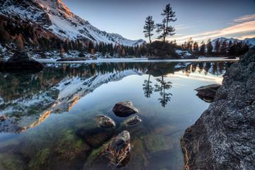 Autumn reflections at Saoseo Lake still partially frozen Poschiavo Valley Canton of Graubuenden Switzerland Europe