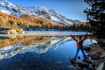 Hiker rejoices in the colorful autumnal landscape around Saoseo Lake Poschiavo Valley Canton of Graubuenden Switzerland Europe