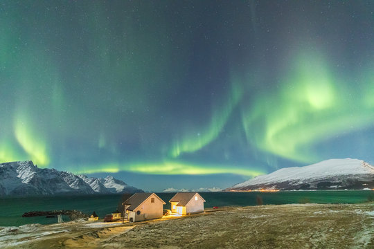 The Northern Lights and stars illuminate the wood houses called Rorbu framed by sea Djupvik Lyngen Alps Troms√∏ Norway Europe