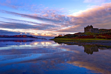 Early morning view of Castle Tioram and Loch Moidart as dawn breaks in a warm colorful sky to form attractive reflections