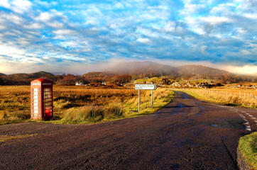 Autumn view of a red telephone box at the side of a quiet road in the remote misty Ardnamurchan moors of the Scottish Highlands