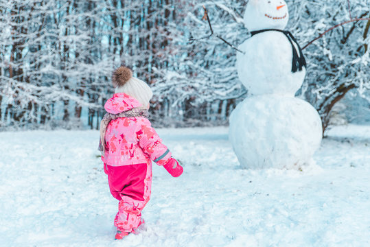 little gild kid in pink winter clothes looking at big snowman