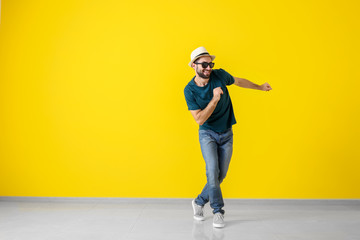 Handsome young man dancing near color wall Wall mural