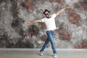 Handsome young man dancing near grunge wall