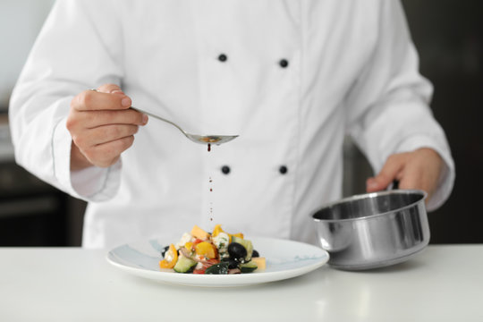 Male chef dressing tasty salad in kitchen, closeup