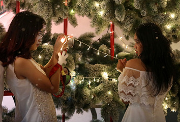 People take pictures with Christmas decorations at a shopping mall in Bangkok