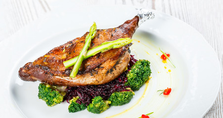 Grilled pork chop steak on the bone with asparagus and broccoli on light wooden background close up. Hot Meat Dishes. Top view