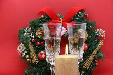 Two glasses of champagne, a golden candle, a wreath on a red background