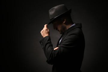 Portrait of detective on dark background