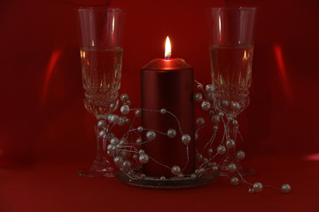 Two glasses of champagne, a red candle, a wreath on a red background.