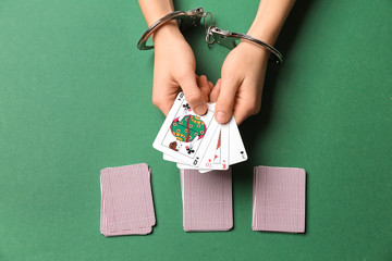 Female hands in handcuffs holding playing cards on color background
