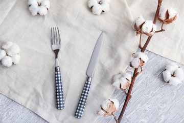 Cutlery, napkin and cotton flowers on white table