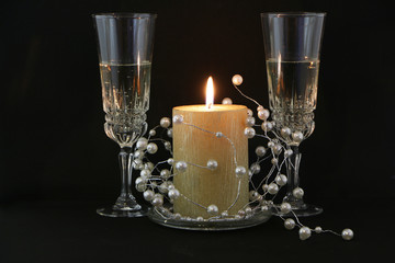 Two glasses of champagne, a red candle, a wreath on a white background.