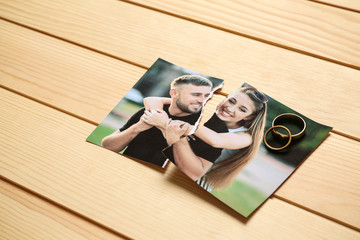 Torn photo of happy couple on wooden background. Concept of divorce