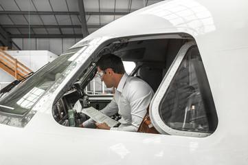 Pilot in cockpit in hangar