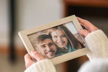 Woman holding photo of happy couple in frame with cracked glass, closeup. Concept of divorce