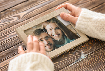 Woman holding photo of happy couple in frame with cracked glass. Concept of divorce