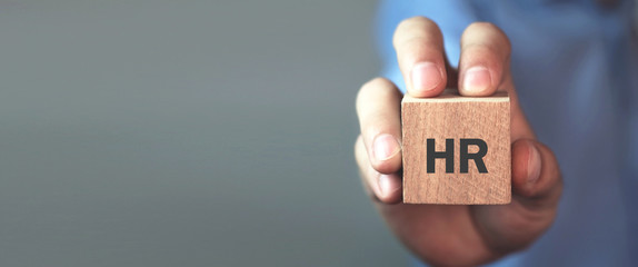 Man holding HR word on wooden cube.
