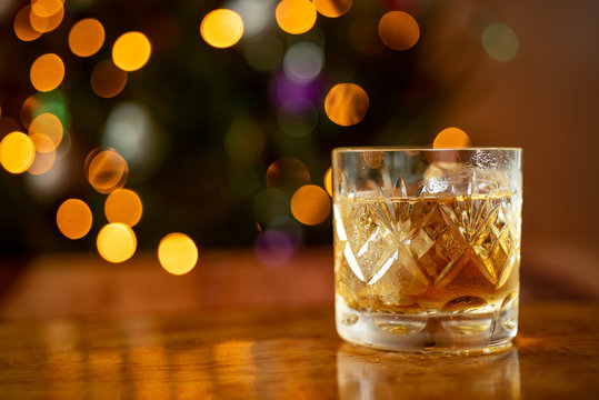 Glass of whiskey bourbon in a crystal glass up close shot Christmas lights background
