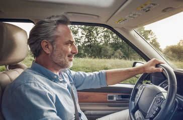 Side view of mature man driving car