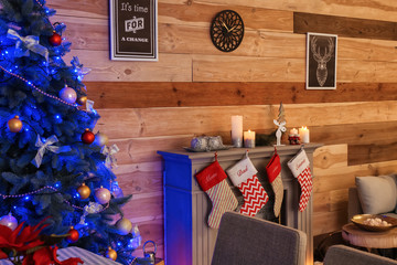 Interior of room with beautiful Christmas fir tree and decorative fireplace