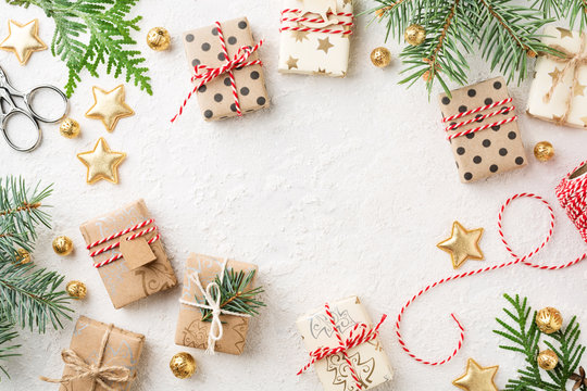 Christmas gift boxes, decorations, bakers twine & spruce on white background. Wrapped gifts, Cristmas preparation. Copy space.