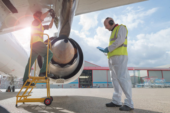 Mechanics working on airplane wing outdoors