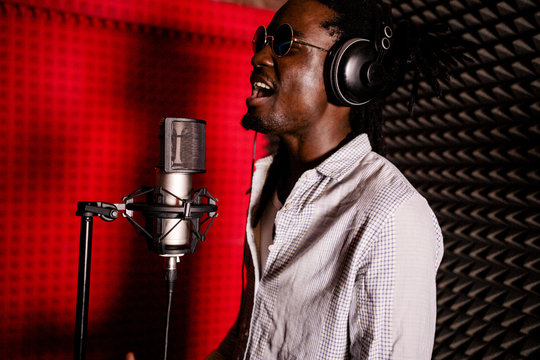 African man with dreadlocks and headphones in the recording Studio singing loudly close-up. Side view
