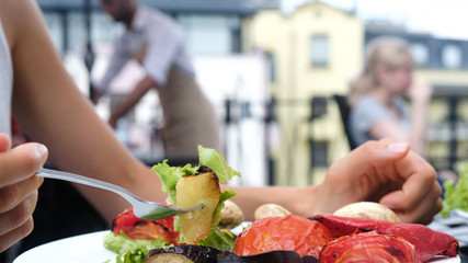 Woman eating a fork with grilled vegetables with fresh salad closeup in the summer outdoors