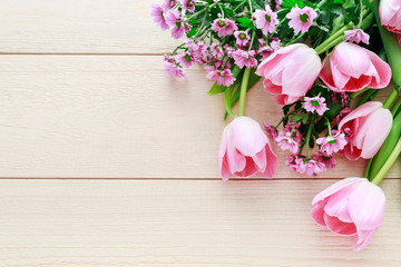 Pink tulips and chrysanthemum flowers on wooden background