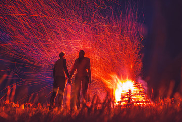 Couple in love standing together by the fire. Valentine, marriage photo.