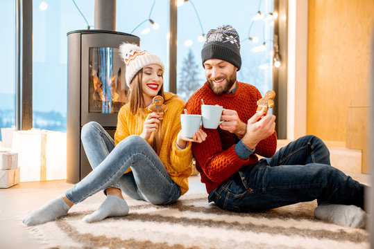 Young couple dressed in bright sweaters sitting together with hot drinks near the fireplace in the modern house in the mountains durnig winter time