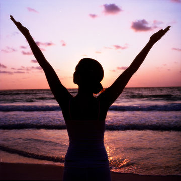 Silhouette of woman practicing yoga on beach at sunset