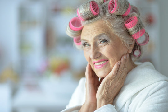 Portrait of senior woman in bathrobe with curlers