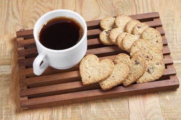 Coffee and tasty cookies in the shape of a heart