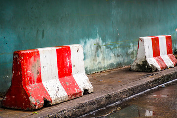 red white concret barrier stop going sign on street stand on footpath green painted old wall background