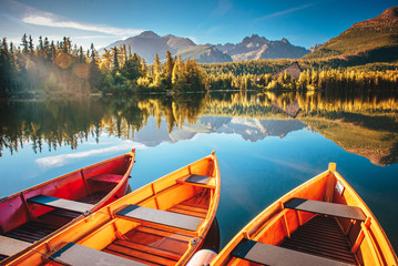 Obraz Morning lake Strbske pleso in Tatra mountains. Colorful boats on the water - fototapety do salonu