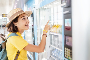 Happy asian woman using a modern beverage vending machine to buy drinks
