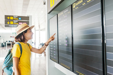 Young asian woman in international airport looking at the flight information timetable board