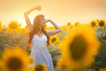 Beautiful young woman in a field of sunflowers
