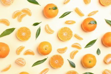 Composition with tangerines and leaves on color background, flat lay