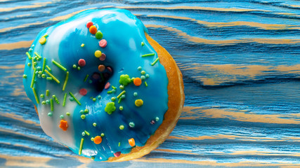 Blue donut on the old blue wooden table, with a clearly visible wood texture