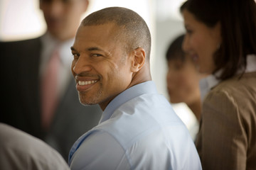 Portrait of a smiling mid-adult businessman looking over his shoulder while standing with his colleagues.