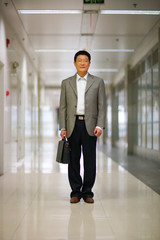 Portrait of a mid-adult man standing in a corridor.