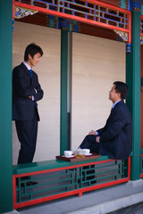 Young adult businessman having tea with a mid-adult male colleague.