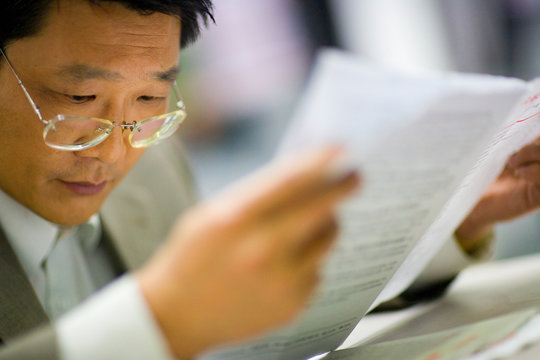 Mid-adult man looking over papers.