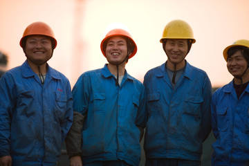 Portrait of mid-adult male construction workers standing on a shipping dock.