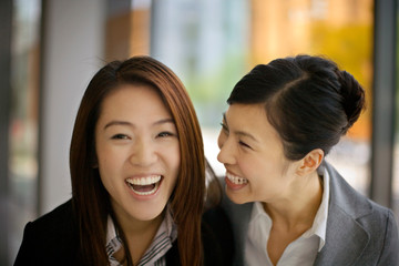 Portrait of two young adult woman laughing together.